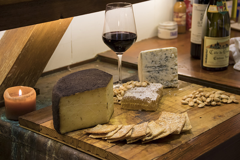 Cheese, wine, crackers and nuts on a wooden table.