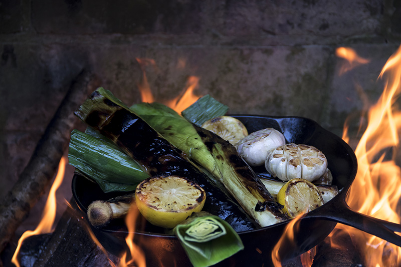 A pan over fire with vegetables in it